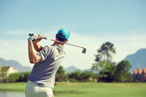 Golfer hitting golf shot with club on course while on summer vac